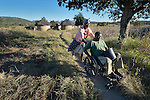Nhaume Makavire pushes her husband, Henry Gwese, on their farm in Charumengwe, Zimbabwe. Gwese's legs were paralyzed by cerebral malaria, yet he and his wife continue farming. He uses an appropriately designed and fitted wheelchair provided by the Jairos Jiri Association with support from CBM-US.