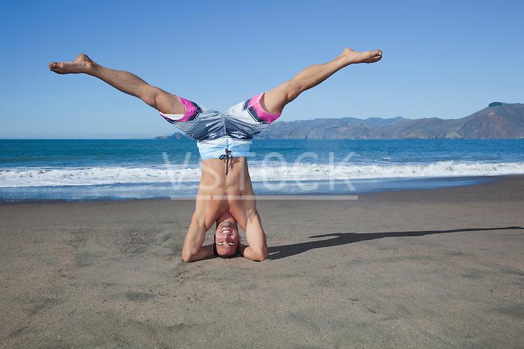 USA, California, San Francisco, portrait of man performing head stand on Baker Beach