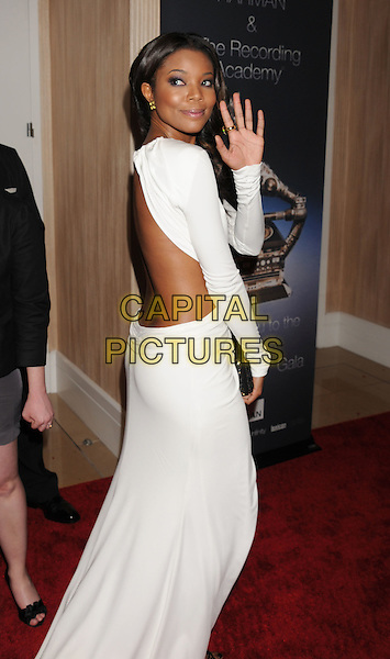 Gabrielle Union.The Clive Davis and The Recording Academy's 2012 Pre-GRAMMY Gala and Salute to Industry Icons at the Beverly Hilton Hotel in Beverly Hills, California, USA..February 11th, 2012.full length white dress cut out away backless looking over shoulder hand waving .CAP/ROT/TM.©Tony Michaels/Roth Stock/Capital Pictures