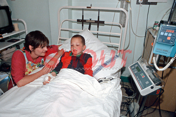 Paediatric nurse talking to a child confined to bed in the paediatric ward. The child is linked to infusion and volumetric pumps. This image may only be used to portray the subject in a positive manner..©shoutpictures.com..john@shoutpictures.com