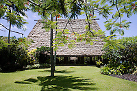 One of the buildings seen from the garden has a traditional steep roof made of woven rushes