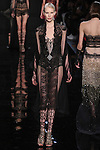 """Model walks runway in an embroideredlace bodysuit with delicate overcoat from the Reem Acra Fall 2016 """"The Secret World of The Femme Fatale"""" collection, at NYFW: The Shows Fall 2016, during New York Fashion Week Fall 2016."""