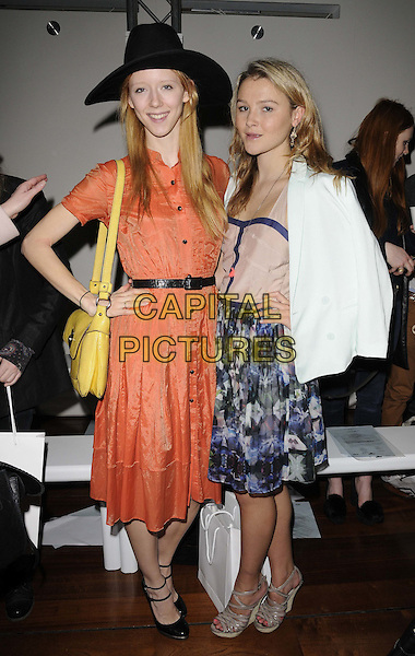 Morwenna Lytton Cobbold & Amber Atherton.attended the Antipodium autumn/winter 2012 salon show, London Fashion Week Day 2, BFC Gallery, Somerset House, The Strand, London, England, UK, 18th February 2012..LFW full length black hat  orange shirt dress yellow bag  blue print skirt wedges white jacket hand on hip  .CAP/CAN.©Can Nguyen/Capital Pictures.