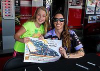 May 30, 2014; Englishtown, NJ, USA; A young fan poses with NHRA funny car driver Alexis DeJoria during qualifying for the Summernationals at Raceway Park. Mandatory Credit: Mark J. Rebilas-