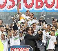 MEDELLÍN -COLOMBIA-21-05-2014. Jugadores del Atlético Nacional levantan el trofeo mientras Juan Carlos Osorio (Der), técnico, recibe del Presidente de la DIMAYOR, Ramón Jesurum (centro abajo), el otro trofeo, para celebrar el título como Campeones de la Liga Postobón I 2014 después de derrotar al Atletico Junior en partido de vuelta de la final jugado en el estadio Atanasio Girardot de la ciudad de Medellín./ Atlético Nacional Players raise the trophy while Juan Carlos Osorio (R), coach, receives the another trophy from Ramon Jesurum (C below), President of DIMAYOR, to celebrate as a champions of Postobon League I 2014 after defeated Atletico Junior in the second leg match of the final played at Atanasio Girardot stadium in Medellin city. Photo: VizzorImage / Felipe Caicedo / Staff