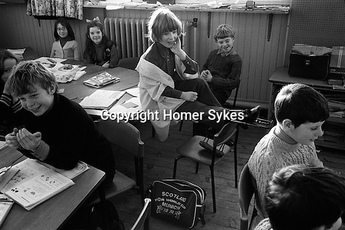 Junior school, schoolboys and schoolgirls in class, young disabled schoolgirl wearing calipers sitting on her shared desk. A Scotland for World Cup Munich 1974 schoolbag is on the floor. Carloway, Isle of Lewis, Outer Hebrides, Scotland. 1974, Shetlands,