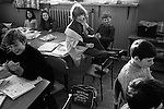 Junior school, schoolboys and schoolgirls in class, young disabled schoolgirl wearing callipers sitting on her shared desk. A Scotland for World Cup Munich 1974 schoolbag is on the floor. Breasclete Isle of Lewis and Harris,   Outer Hebrides, Scotland. 1974,