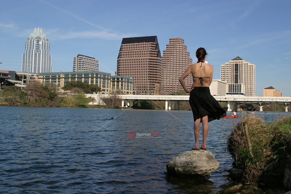 Dog swims across Town Lake as the owner looks on at town lake austin, TX