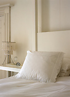 Detail of a pillowcase trimmed with 'broderie anglaise' and a beaded lamp in an all white bedroom
