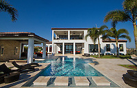 Luxury Home worth several million dollars pool with palm trees and blue sky