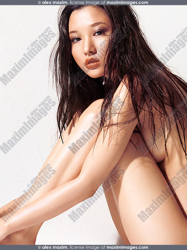 Sensual portrait of a beautiful young asian woman with shiny naked body sitting in front of a white wall