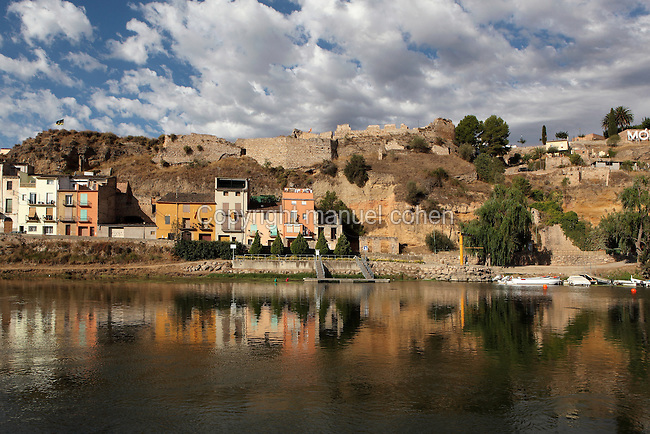 Houses in Mora d'Ebre on the right bank of the Ebro river, with the ruined castle of the Barony of Entenca on the hill above, Ribera d'Ebre, Tarragona, Spain. Picture by Manuel Cohen