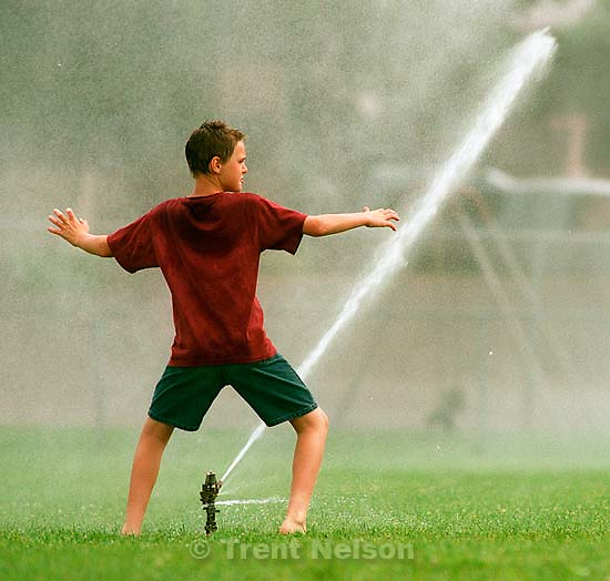 Kids playing in sprinklers at Douglas School.<br />