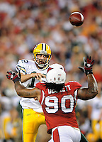 Aug. 28, 2009; Glendale, AZ, USA; Green Bay Packers quarterback (12) Aaron Rodgers throws a pass under pressure in the first half against the Arizona Cardinals during a preseason game at University of Phoenix Stadium. Mandatory Credit: Mark J. Rebilas-