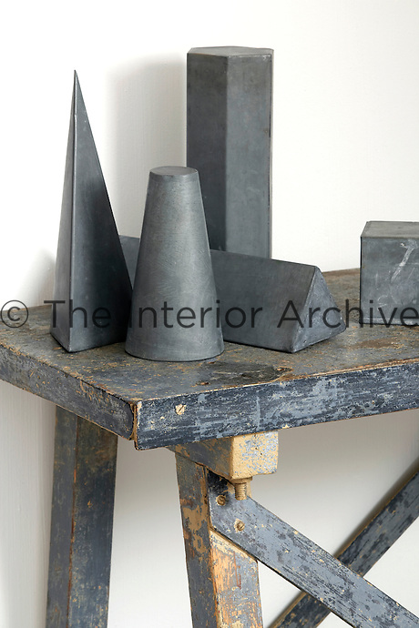 The geometric zinc shapes on this rough-hewn trestle table were once used as teaching aids in schools