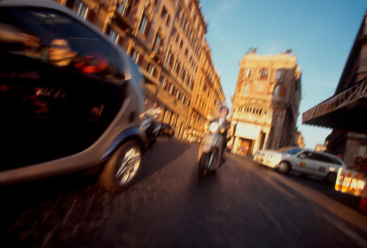 Rome, Italy, A classic example of the Italian love for cars, innovation and the ability to park in the tiniest of spaces: woman in automobile at speed near Piazza di Spagna (the Spanish Steps) at sunset..