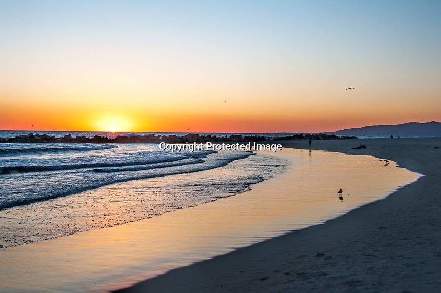 The sun sets on a winter day at Venice Beach, California.