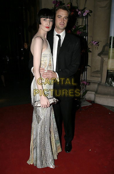 ERIN O'CONNOR & JAMIE THEAKSTON.The British Fashion Awards, Victoria and Albert (V&A) Museum, London, November 2nd 2004..full length couple clutch bag .Ref: AH.www.capitalpictures.com.sales@capitalpictures.com.©Capital Pictures.