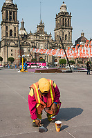 Scraping chewing gum from the zocalo. Day of the dead in the Zocalo 2017, Mexico City, Mexico