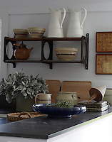Close up of jugs and pots on a salvaged metal bracket shelving system in the kitchen