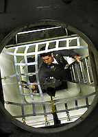 Lt. Jerry Graven, a Board of Inspection and Survey (INSURV) officer, inspects cargo netting aboard the Nimitz- class aircraft carrier USS Abraham Lincoln (CVN 72).<br />