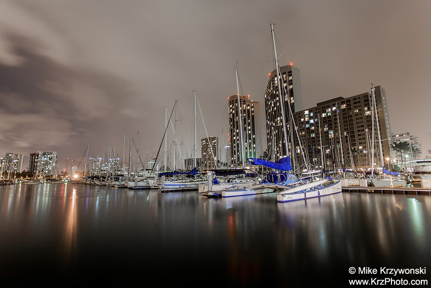 Boats and city lights reflecting off the water at night in the Ala Wai boat harbor in Honolulu, Oahu