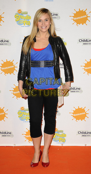 """SARAH SMITH of SAME DIFFERENCE.At the """"Spongebob Squarepants - The Sponge who could Fly"""" Gala performance at the Hammersmith Apollo, London, England. .March 5th 2009 .full length black jacket blue top waist belt red shoes studded cropped leggings trousers clutch bag leather sara .CAP/CAN.©Can Nguyen/Capital Pictures."""