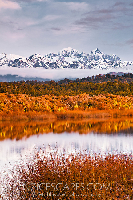 Alpine glow over the Southern Alps and lagoon from near Okarito, Westland National Park, West Coast, New Zealand