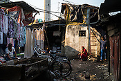 A woman sits outside her hut at the Laundromat in Dhobighat in India's financial capital, Mumbai, India. Hundreds of families live at the dhobi ghat, and their families have been doing the laundry work for generations.