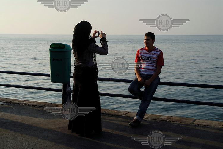 A girl takes a photograph of her boyfriend on the Corniche.