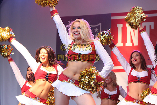 GOLD RUSH - THE SAN FRANCISCO 49ers CHEERLEADERS.NFL Fan Rally at Trafalgar Square,  London, England..October 30th 2010.stage show costume uniform pom poms gold red white arms in air dancing gesture half length belly stomach midriff skirt top.CAP/JIL.©Jill Mayhew/Capital Pictures