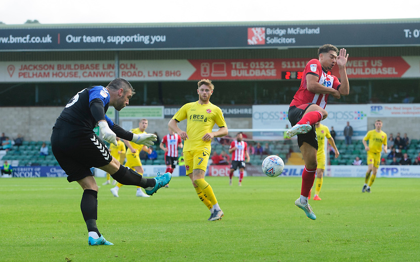 Lincoln City's Tyler Walker charges down a clearance from Fleetwood Town's Matt Gilks<br /> <br /> Photographer Chris Vaughan/CameraSport<br /> <br /> The EFL Sky Bet League One - Lincoln City v Fleetwood Town - Saturday 31st August 2019 - Sincil Bank - Lincoln<br /> <br /> World Copyright © 2019 CameraSport. All rights reserved. 43 Linden Ave. Countesthorpe. Leicester. England. LE8 5PG - Tel: +44 (0) 116 277 4147 - admin@camerasport.com - www.camerasport.com