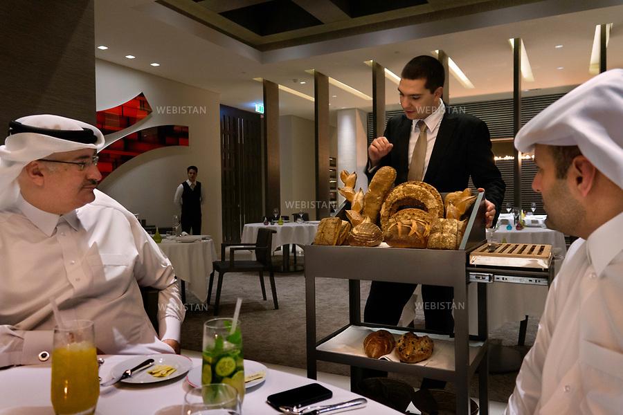 Qatar, Doha.<br /> Two men dining at Grand Regency Hotel, at Doha bay.<br /> Qatar is one of the Arab peninsular emirates, on the Persian Gulf shoreline. Bordered by Saudi Arabia, Qatar's economy relies on oil and gas. Being the world's fourth-largest gas exporter, gas remains the major driver of Qatar's economy. The emirate is governed by Sheikh Tamim bin Hamad Al Thani who became at the age of 33 Emir of Qatar on 25 June 25th, 2013 after his father's abdication. He is the youngest emir at the head of an Arab State.<br /> On June 5th, 2017, Saudi Arabia, the United Arab Emirates, Egypt, Bahrain, Yemen, Libya, Mauritania, the Maldives, and Mauritius broke off diplomatic relations with Qatar, accusing the emirate of supporting several terrorist groups. As its Gulf neighbours enforced the closure of all land, air and sea borders to Qatar, the country is quarantined.<br /> <br />Qatar, Doha.<br />Deux hommes d&icirc;nent au Grand Regency Hotel, situ&eacute; sur la baie de Doha.<br />Le Qatar est l'un des &eacute;mirats du Moyen-Orient de la p&eacute;ninsule du golfe persique. Voisin de l'Arabie Saoudite, l'&eacute;conomie qatarie trouve son &eacute;quilibre gr&acirc;ce &agrave; la vente de gaz naturel dont il est le quatri&egrave;me vendeur au monde, avant la vente de p&eacute;trole. L'&eacute;mirat est dirig&eacute; par l'&eacute;mir Tamim ben Hamad Al Thani, qui succ&egrave;de le 25 juin 2013 &agrave; son p&egrave;re alors qu'il n'a que 33 ans, et devient alors le plus jeune chef d'&Eacute;tat du monde arabe.<br />Le 5 juin 2017, l'Arabie Saoudite, les &Eacute;mirats arabes unis, l'&Eacute;gypte, Bahre&iuml;n, le Y&eacute;men, la Libye, la Mauritanie, les Maldives et l'&icirc;le Maurice rompent toute relation diplomatique avec le Qatar, l'accusant de soutenir divers groupes terroristes. L'&eacute;mirat est alors mis sous quarantaine avec la fermeture des fronti&egrave;res terrestres, a&eacute;riennes et maritimes.