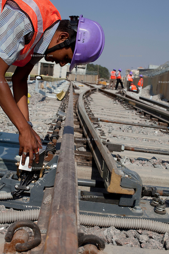 An ALSTOM employee (in purple hardhat) fixes the connectivity on the MJ81 (Intech) Point Machines at the Baiyappanahalli depot station in Bangalore, Karnataka, India on 10th March 2011. .Photo by Suzanne Lee/Abaca Press