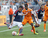 New England Revolution midfielder Lee Nguyen (24) crosses the ball as Houston Dynamo defender Kofi Sarkodie (8) defends. In a Major League Soccer (MLS) match, the New England Revolution (blue/white) defeated Houston Dynamo (orange), 2-0, at Gillette Stadium on April 12, 2014.