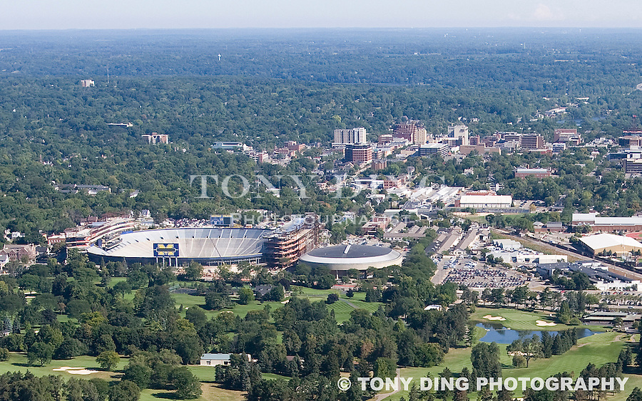 "15 August 2008: Aerial view of Michigan Stadium, background past foreground Michigan Golf Course, undergoing major renovations and expansion in Ann Arbor, MI. The three year, $226 million project will add 82 luxury suites, a new press box, improved stadium seating and concourse fans amenities, as well as premium club seating sections that will eventually bring the ""Big House"" capacity to over 108,000. Project completion is scheduled for August 2010."