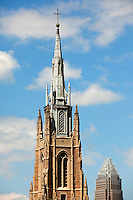 The spires of Covenant Presbyterian Chruch, a church in uptown / downtown / Center City Charlotte NC, rise into the Carolina blue sky.
