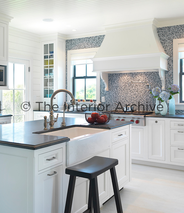 A signature wall in this country-style kitchen is covered in grey and white mosaic tiles