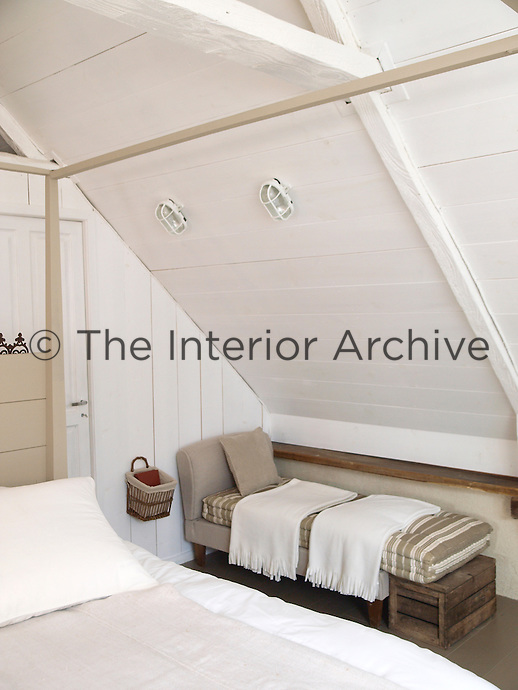 A white-painted bedroom under the eaves of the cottage