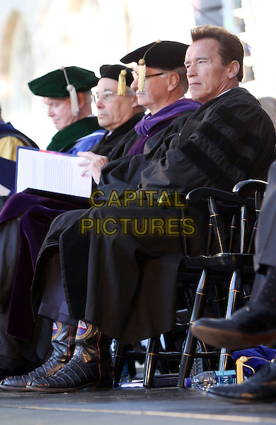ARNOLD SCHWARZENEGGER.California Governor and actor Arnold Schwarzenegger at Emory University Commencement with Arnold Schwarzenegger as the Keynote Speaker and honorary degree recipient, Atlanta, GA, USA..May 10th, 2010.full length cloak robe sitting side profile chair cowboy boots  black .CAP/ADM/DH.©Dan Harr/AdMedia/Capital Pictures.