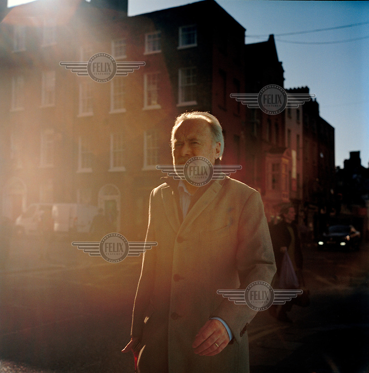 A man walks in the sun on Baggot Street.