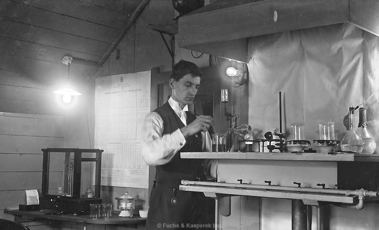 A man works on an experiment in his laboratory. Circa 1916.