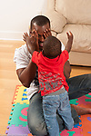 Father playing peek a boo game with 12 month old baby boy covering face with hands vertical