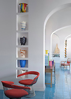 A pair of red armchairs by Warren Platner appears to dance on the blue ceramic tiled floor of the reception area