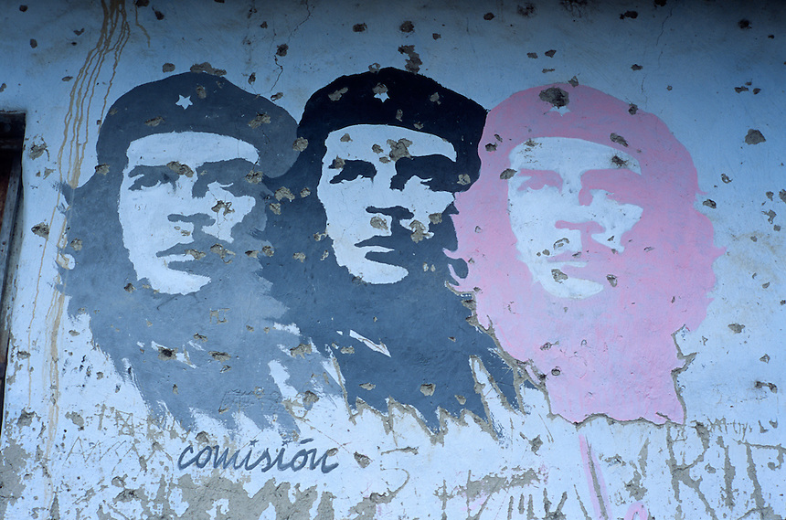 "Painted images of Ernesto ""Che"" Guevara stare from a pock-marked wall in La Higuera, Bolivia, Saturday, Nov. 13, 2004. Guevara was captured by the Bolivian army in 1967 in a nearby valley and executed in La Higuera days later. Guevara and fellow communist guerillas were attempting to launch a continent-wide revolution modeled on Guevara's success in Cuba in the late 1950s. The Bolivian government recently began promoting the area where he fought, was captured, killed and burried for 30 years as the ""Ruta del Che,"" or Che's Route. (Kevin Moloney for the New York Times)"