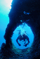 Diver with bubbles swimming through hole in rock, France, Marseille, Mediterranean Sea