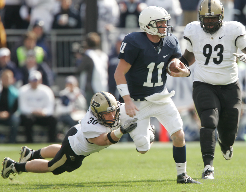 State College, PA - 10/15/2011:  Penn State quarterback Matt McGloin attempts to avoid a diving tackle by Purdue LB Joe Holland (30).  Penn State defeated Purdue by a score of 23-18 on October 15, 2011, homecoming, at Beaver Stadium...Photo:  Joe Rokita / JoeRokita.com..Photo ©2011 Joe Rokita Photography