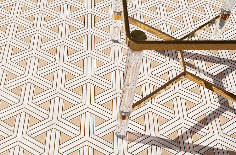 Y Weave, a stone waterjet mosaic, show in honed Lagos Gold, Cloud Nine, and brass liners, is part of the Miraflores Collection by Paul Schatz for New Ravenna.