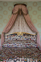 Detail of a  quilted bed cover and matching headboard