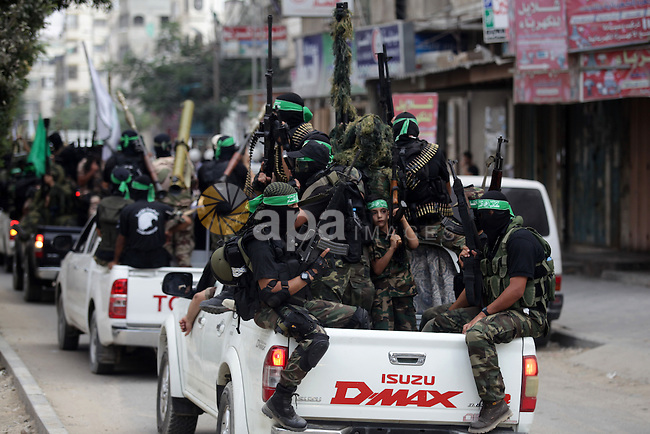 Palestinian militant members of the military Hamas wing Izz Ad-Dine Al-Qassam Brigades are seen during a march along the streets of Al Shatee refugee camp in Gaza City, 21 September 2013. Photo by Ashraf Amra